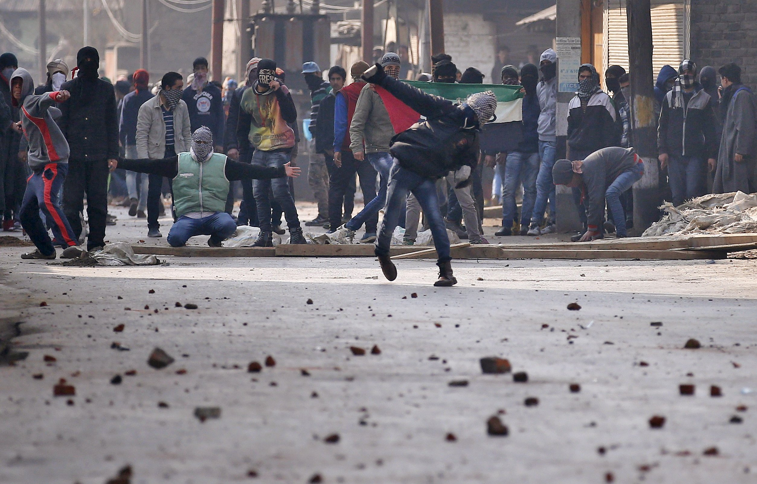 A Kashmiri protester throws a stone towards Indian police during a protest in Srinagar